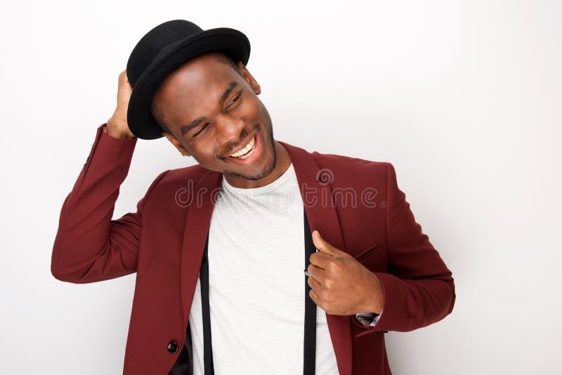 Homem afro-americano feliz que levanta com blazer e chapéu contra o fundo branco fotos de stock