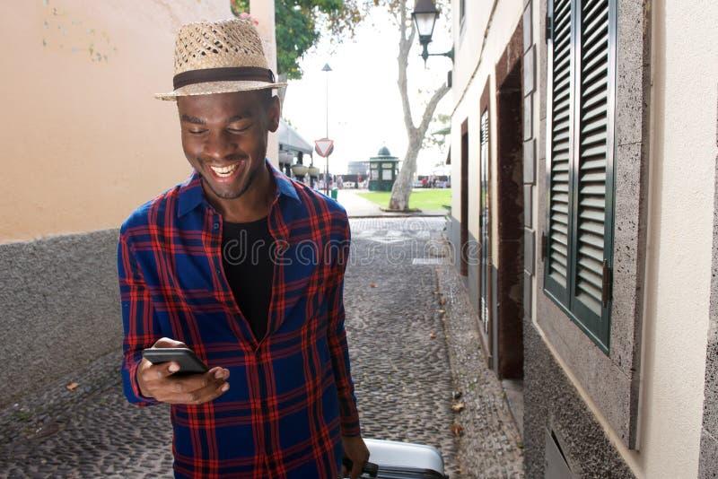 Homem afro-americano feliz que olha o telefone celular ao andar na rua com mala de viagem imagens de stock royalty free
