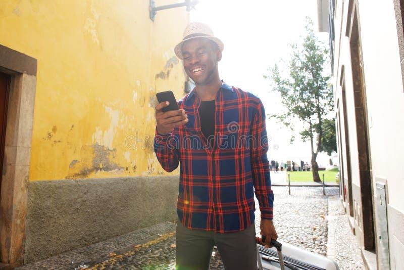 Homem afro-americano feliz que olha o telefone celular ao andar na rua com saco da mala de viagem fotografia de stock