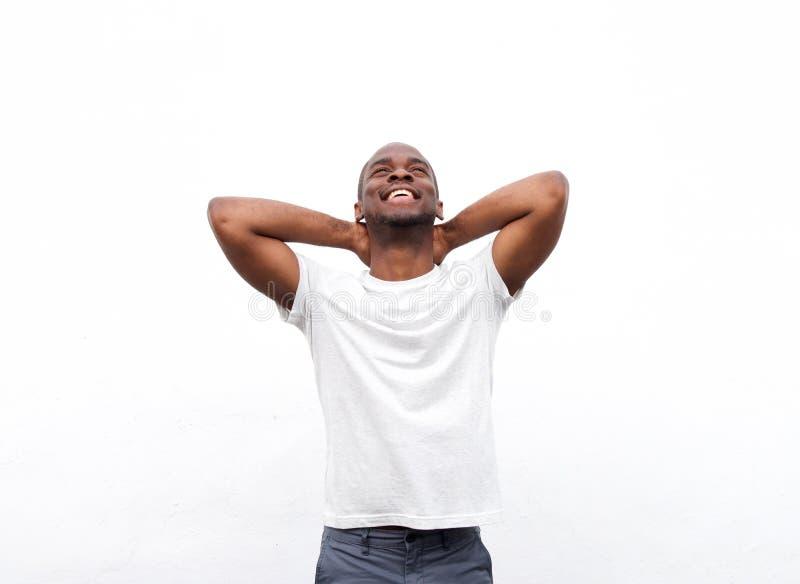 Homem afro-americano feliz que relaxa com mãos atrás da cabeça contra o fundo branco fotografia de stock royalty free