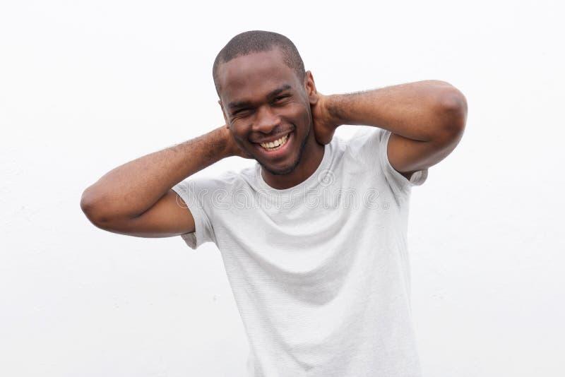 Homem afro-americano feliz que relaxa com mãos atrás da cabeça contra a parede branca foto de stock