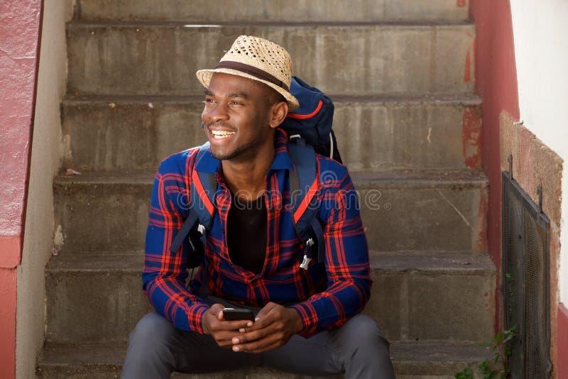 Homem afro-americano feliz que relaxa em etapas com trouxa e telefone celular foto de stock royalty free