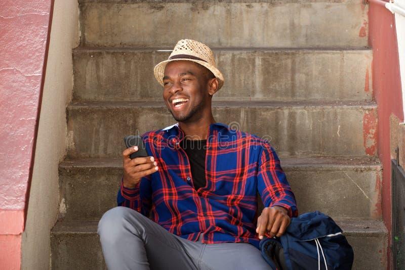 Homem afro-americano feliz que relaxa em etapas com trouxa e telefone celular fotos de stock royalty free