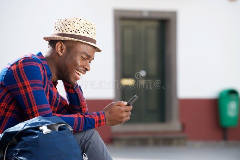 Homem afro-americano feliz que relaxa fora e que olha o telefone celular fotos de stock royalty free
