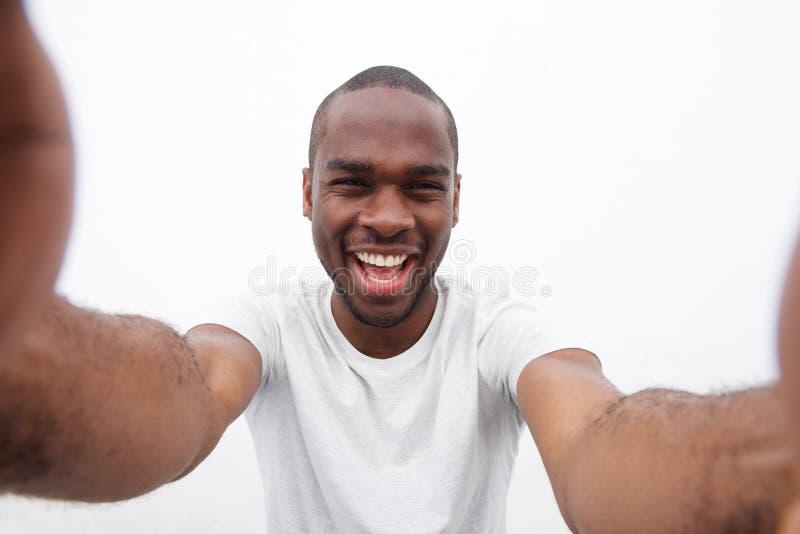 Homem afro-americano feliz que ri ao falar o selfie imagem de stock