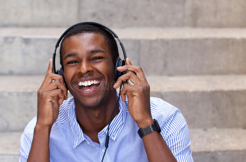 Homem afro-americano feliz que ri com fones de ouvido fotos de stock