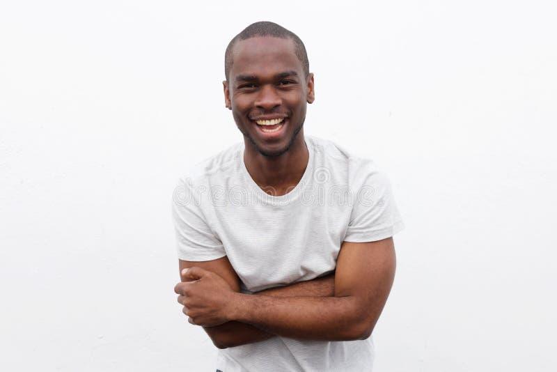 Homem afro-americano feliz que ri com os braços cruzados ao levantar contra o fundo branco fotos de stock