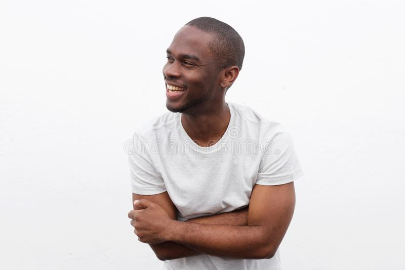 Homem afro-americano feliz que ri com os braços cruzados e que olha afastado contra o fundo branco fotos de stock royalty free