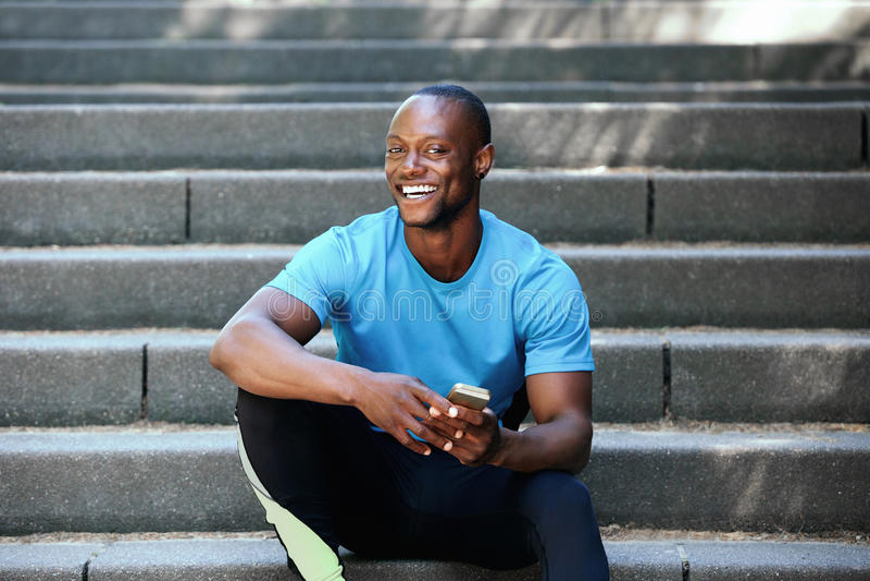 Homem afro-americano feliz que senta-se em escadas com telefone celular imagem de stock royalty free