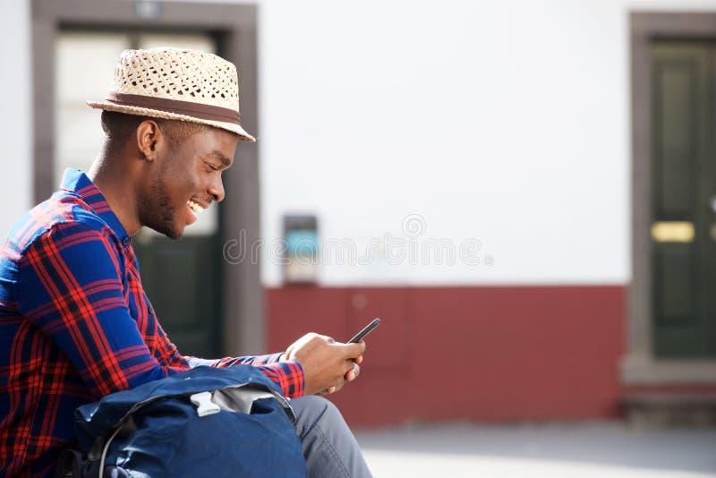 Homem afro-americano feliz que senta-se fora e que olha o telefone celular imagens de stock royalty free