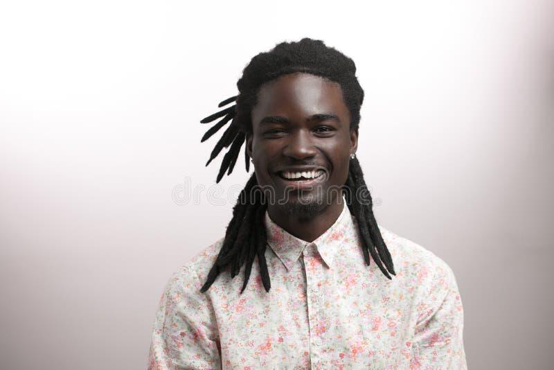 Homem afro-americano feliz que sorri no fundo branco do estúdio Retrato masculino afro-americano do perfil imagem de stock royalty free
