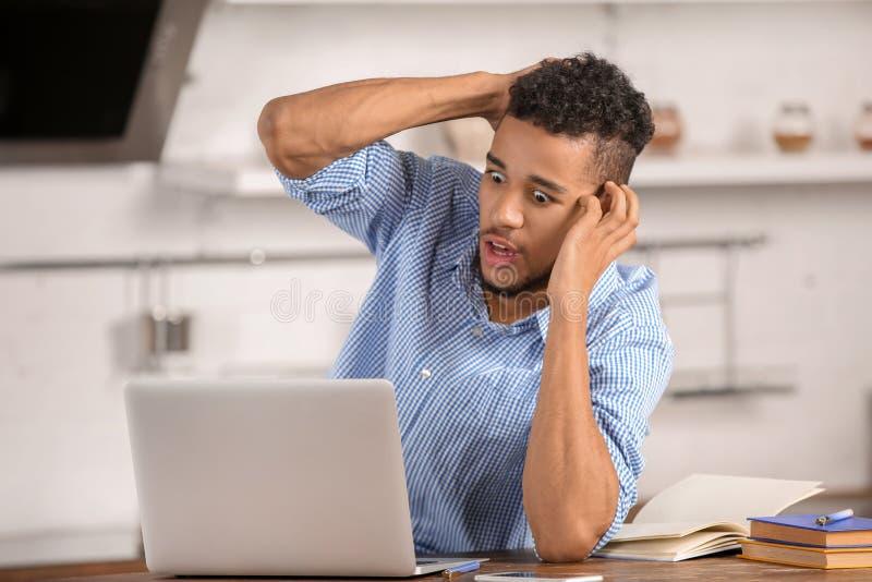 Homem afro-americano forçado com o portátil na cozinha imagens de stock