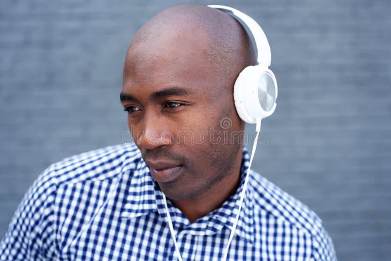 Homem afro-americano fresco com os fones de ouvido que olham afastado imagem de stock