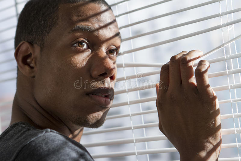 Homem afro-americano nervoso na janela, horizontal imagem de stock royalty free