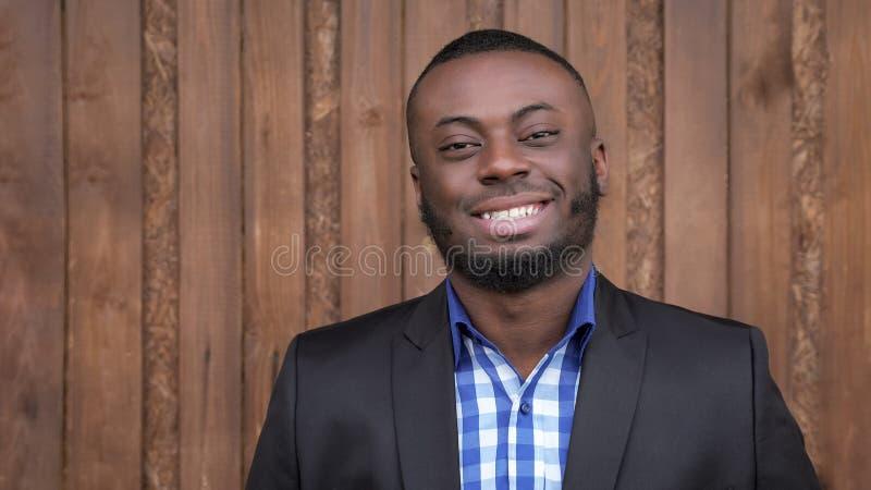 Homem afro-americano no terno que sorri e que olha a câmera no fundo de madeira escuro fotografia de stock