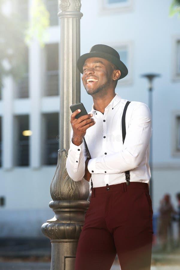 Homem afro-americano novo à moda com suspensórios e telefone celular na cidade foto de stock royalty free