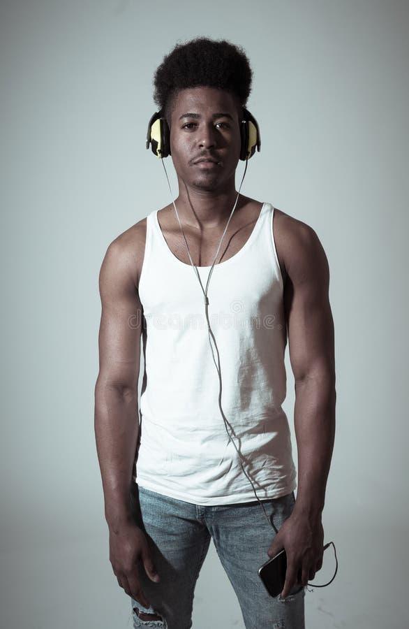 Homem afro-americano novo atrativo com os fones de ouvido que dan?am e que cantam ? m?sica no m?bil na luz do disco fotografia de stock