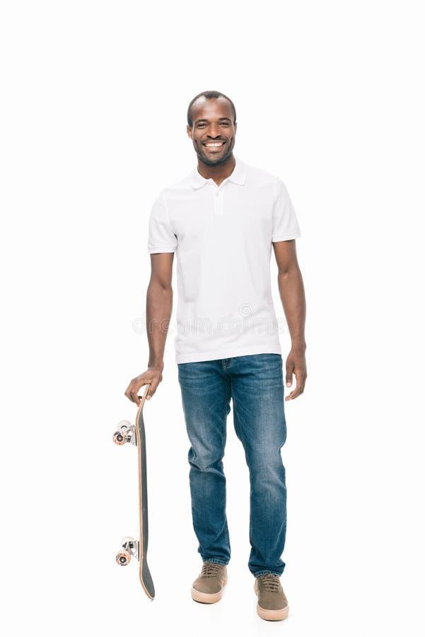 homem afro-americano novo considerável com skate que sorri na câmera fotos de stock