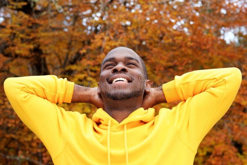 Homem afro-americano novo considerável contra as folhas de outono no fundo que sorri com mãos atrás da cabeça foto de stock