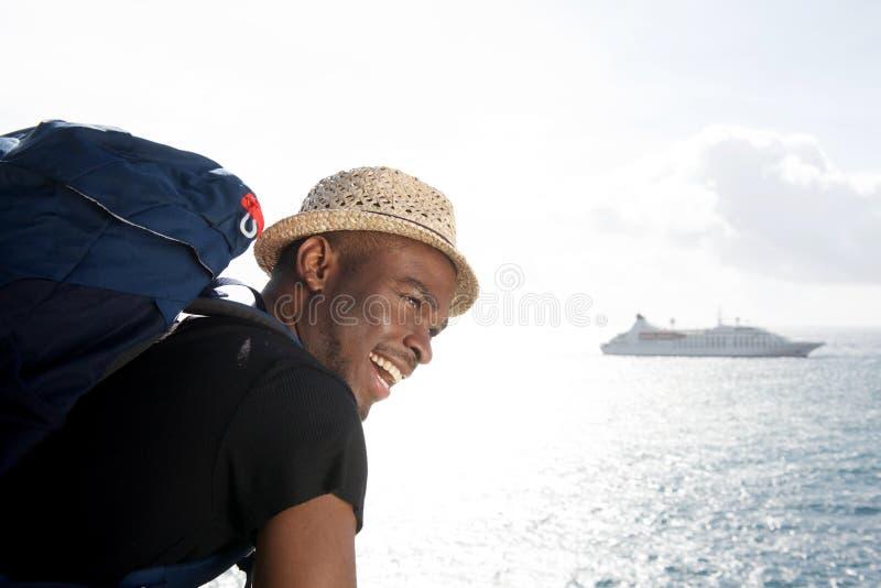 Homem afro-americano novo considerável do curso que sorri pelo mar com o navio de cruzeiros no fundo foto de stock