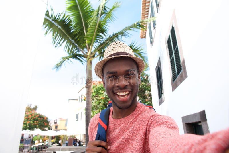 Homem afro-americano novo considerável que sorri ao tomar o selfie em férias fotografia de stock royalty free