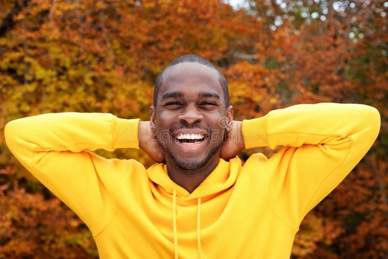Homem afro-americano novo considerável que sorri com as folhas de outono no fundo e nas mãos atrás da cabeça fotografia de stock