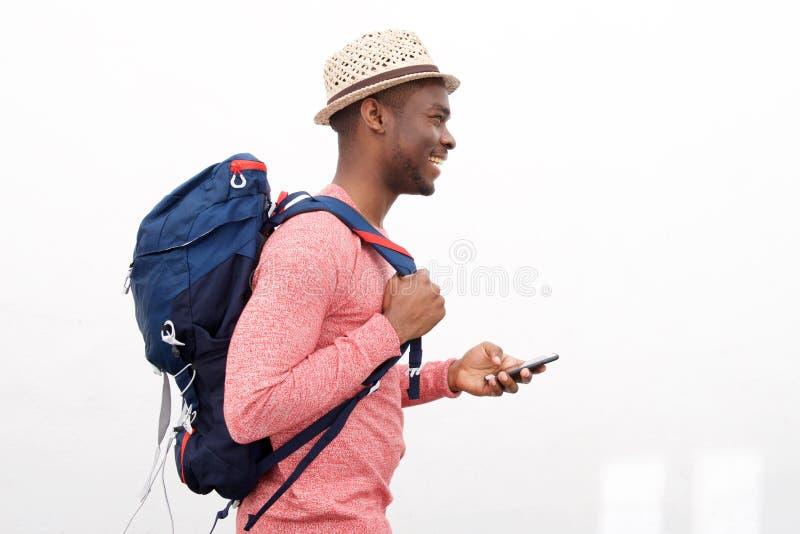 Homem afro-americano novo considerável que sorri com telefone celular e saco contra o fundo branco imagens de stock royalty free