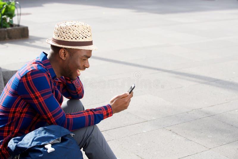 Homem afro-americano novo considerável que sorri com telefone fora imagem de stock