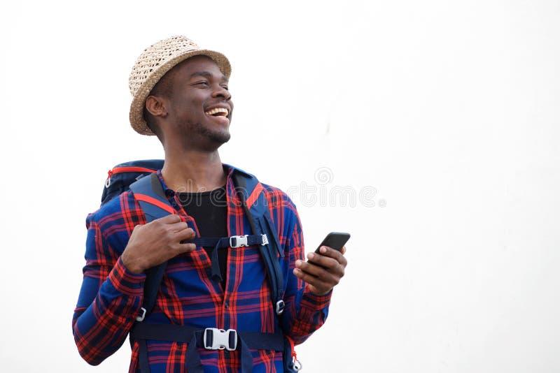 Homem afro-americano novo considerável que sorri com trouxa e telefone celular contra o fundo branco isolado imagem de stock royalty free