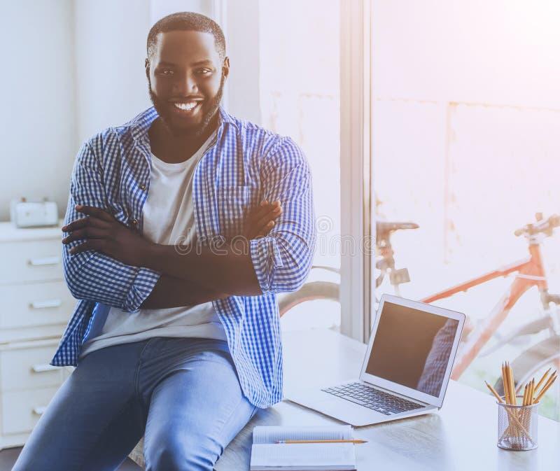 Homem afro-americano novo da barba que senta-se na tabela imagem de stock royalty free