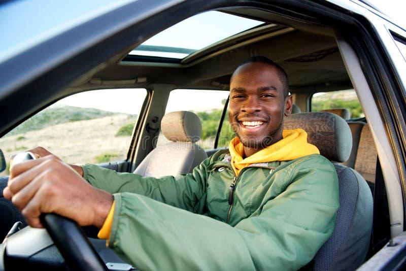 Homem afro-americano novo de sorriso que conduz o carro foto de stock royalty free