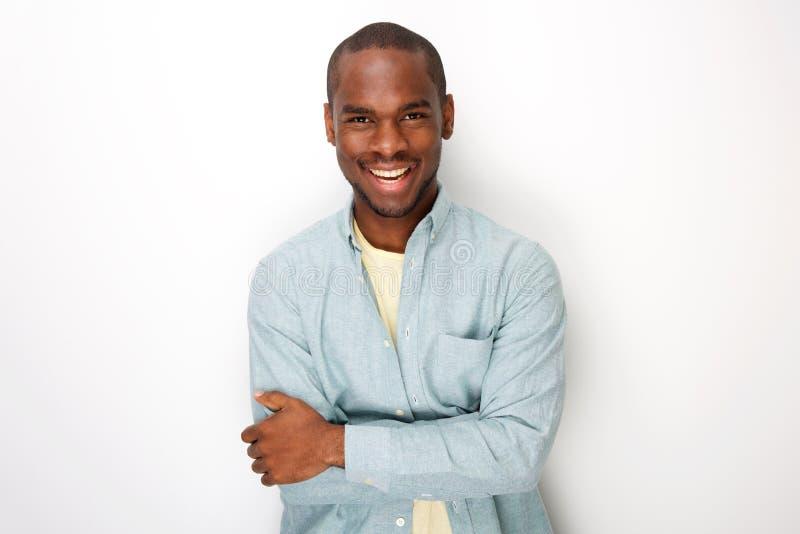Homem afro-americano novo de sorriso que sorri com a camisa pelo fundo branco imagem de stock royalty free