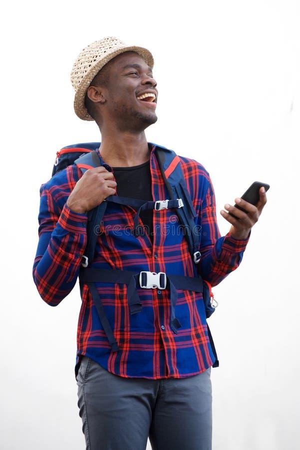 Homem afro-americano novo do curso com trouxa e telefone celular contra o fundo branco isolado fotografia de stock royalty free