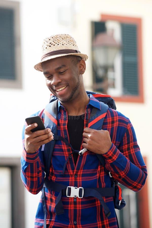Homem afro-americano novo do curso que olha o telefone celular ao andar na rua com trouxa fotografia de stock royalty free