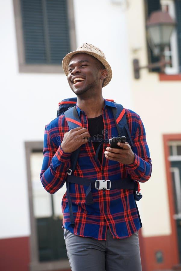Homem afro-americano novo do curso que ri com telefone celular ao andar na rua com trouxa imagem de stock
