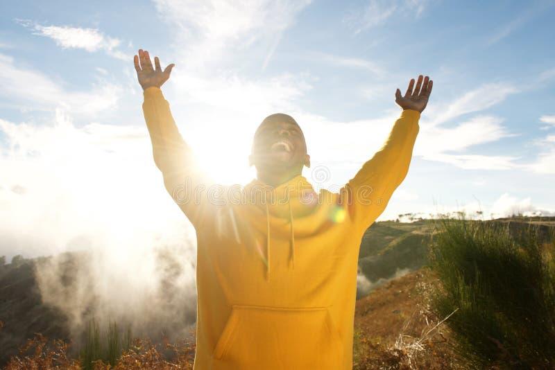 Homem afro-americano novo feliz com os braços aumentados no ar fora imagens de stock