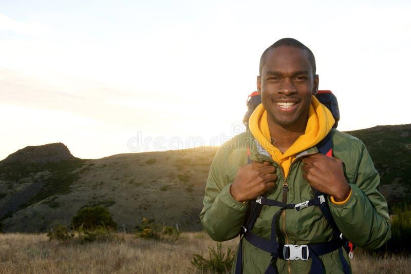 Homem afro-americano novo feliz com com a trouxa que sorri com nascer do sol no fundo fotos de stock
