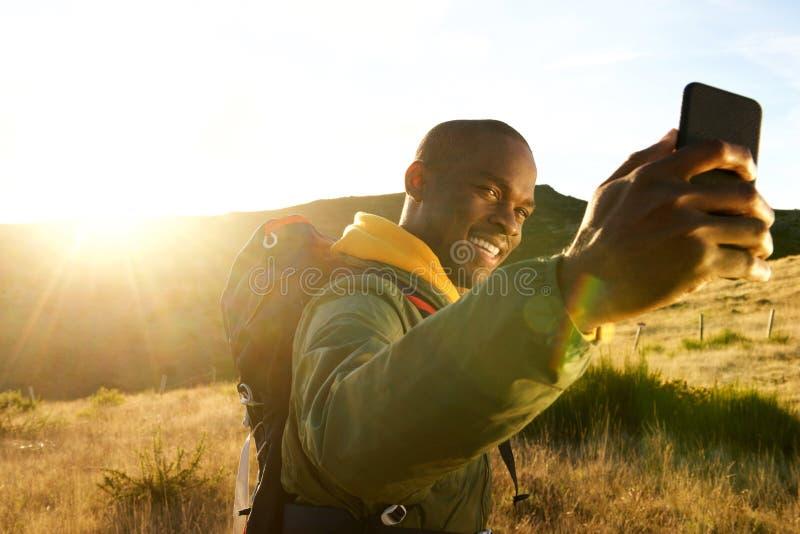 Homem afro-americano novo feliz que caminha nas montanhas que tomam o selfie com nascer do sol no fundo fotografia de stock royalty free