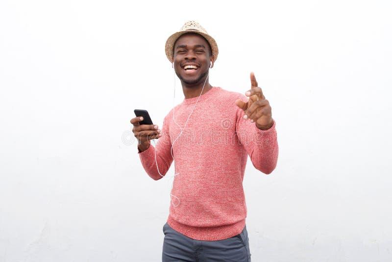 Homem afro-americano novo feliz que escuta a música com telefone celular e fones de ouvido contra o fundo branco foto de stock