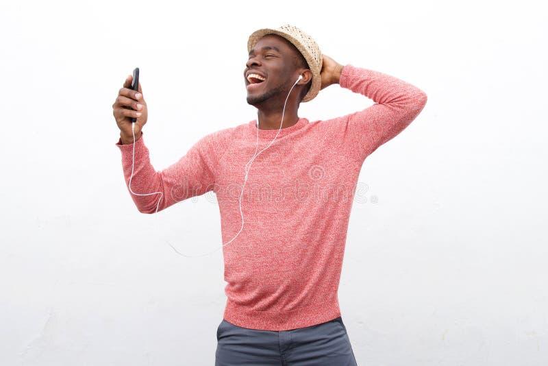 Homem afro-americano novo feliz que escuta a música com telefone e os fones de ouvido espertos contra o fundo branco imagem de stock royalty free