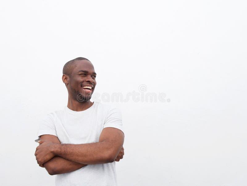 Homem afro-americano novo feliz que ri com os braços cruzados contra o fundo branco fotos de stock