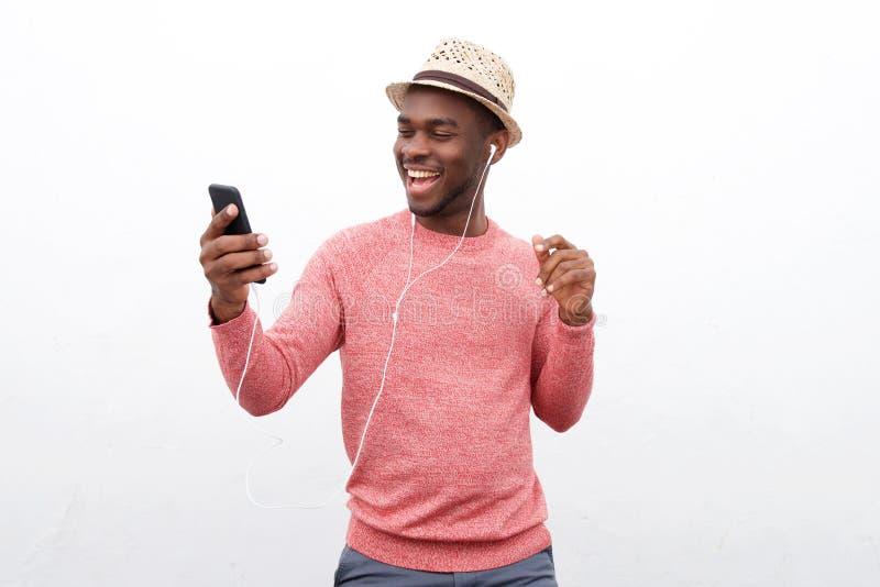 Homem afro-americano novo fresco que escuta a música com fones de ouvido e telefone celular imagens de stock royalty free