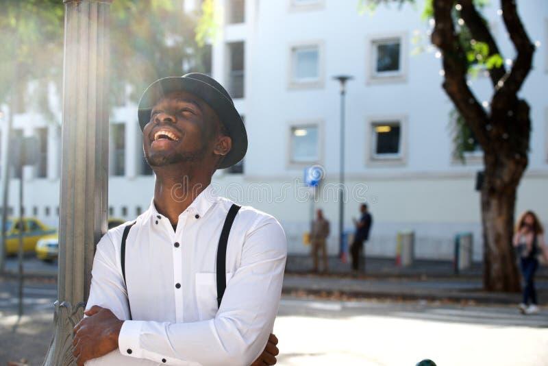 Homem afro-americano novo na moda com chapéu que ri na cidade imagem de stock