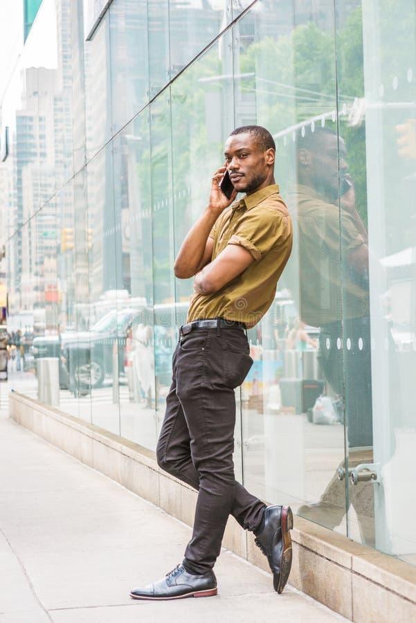 Homem afro-americano novo que chama o telefone celular na rua no Ne imagens de stock