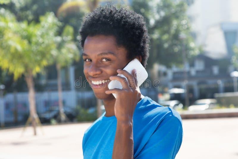 Homem afro-americano novo que fala no telefone celular foto de stock royalty free