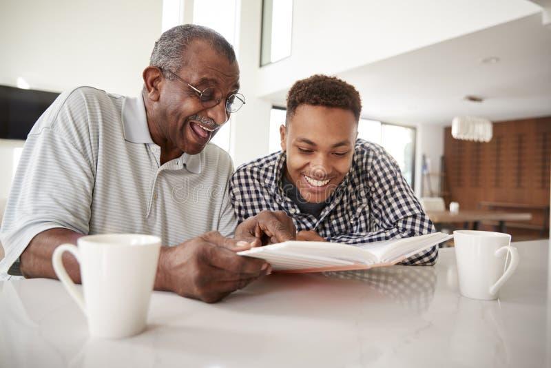 Homem afro-americano novo que olha um álbum de fotografias em casa com seu avô, fim acima fotos de stock royalty free