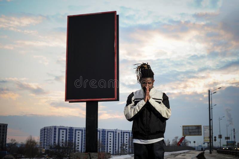 Homem afro-americano novo que reza no fundo da cidade fotografia de stock