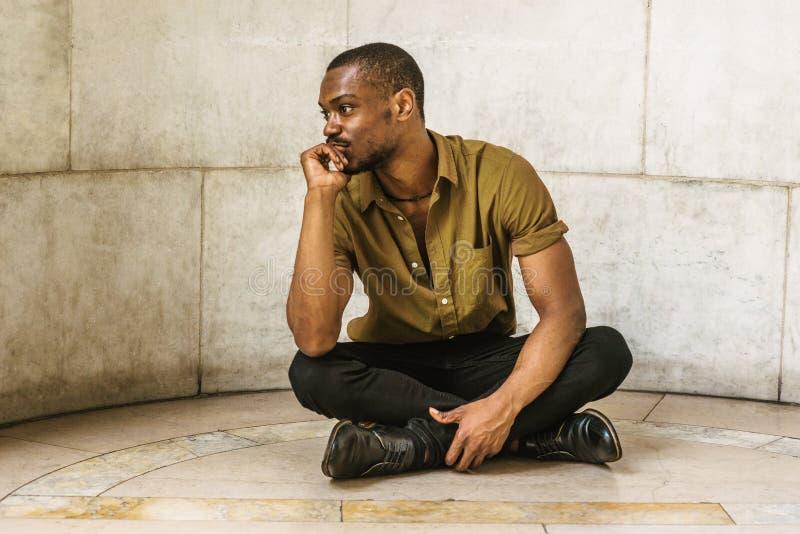 Homem afro-americano novo que senta-se na terra em New York, thinki fotografia de stock