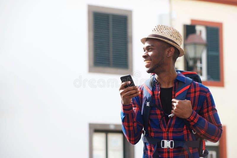 Homem afro-americano novo que sorri com telefone celular ao andar na rua com trouxa fotografia de stock