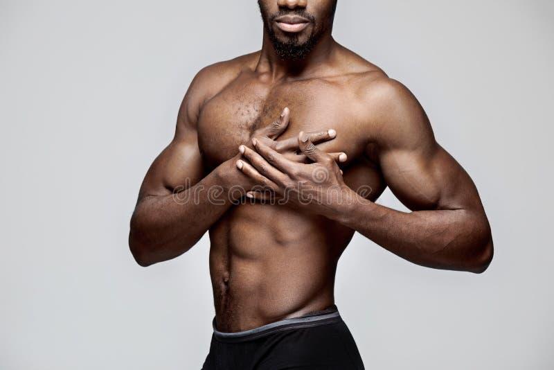Homem afro-americano novo que tem uma dor no coração Cardíaco de ataque foto de stock